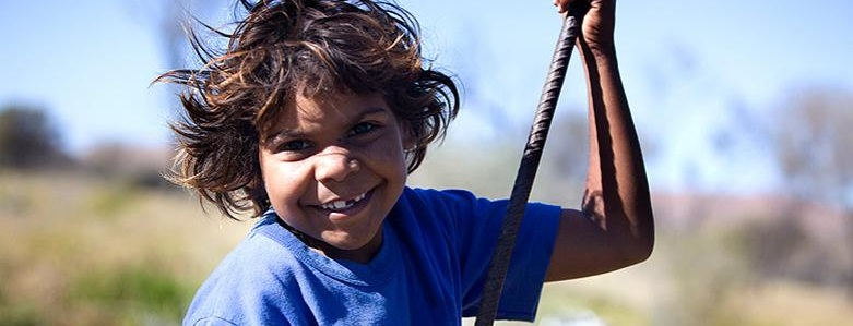 A young Aboriginal boy is smiling at the camera